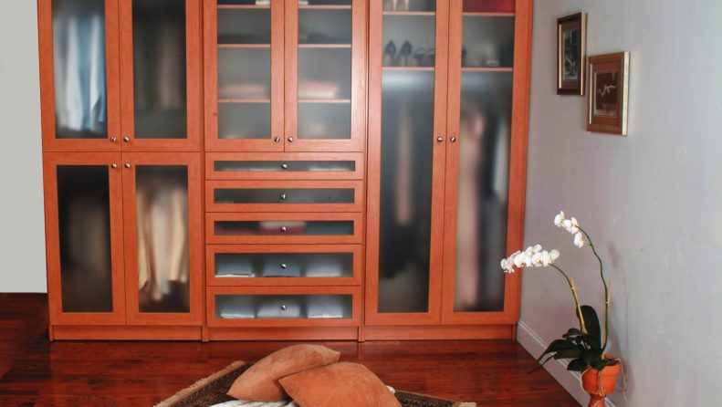 Organized wardroble closet with wood finish