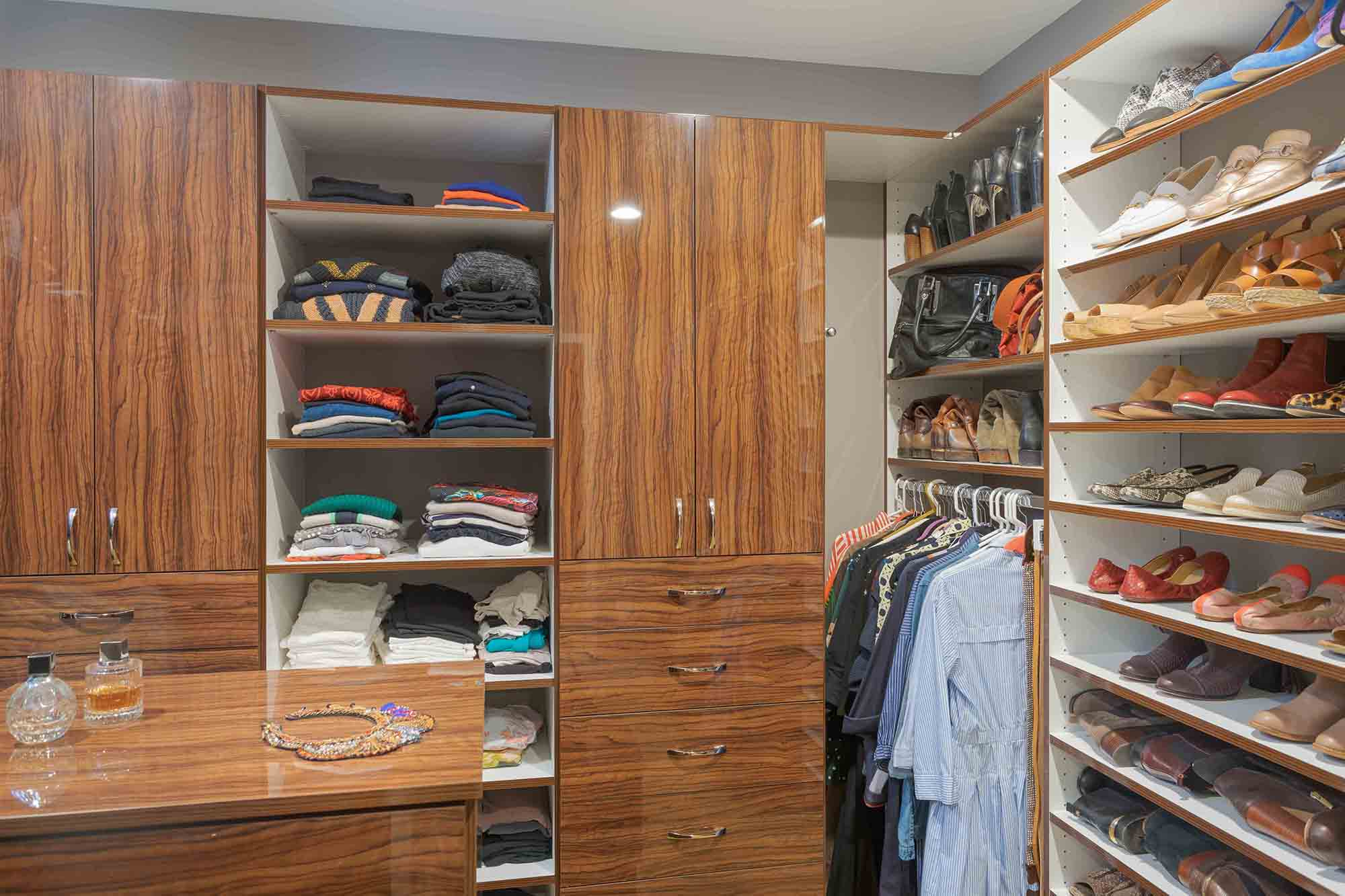 Men's walk in closet organized with shoe shelves