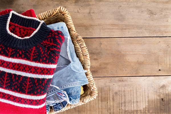 seasonal clothes organized neatly in reach-in closet baskets