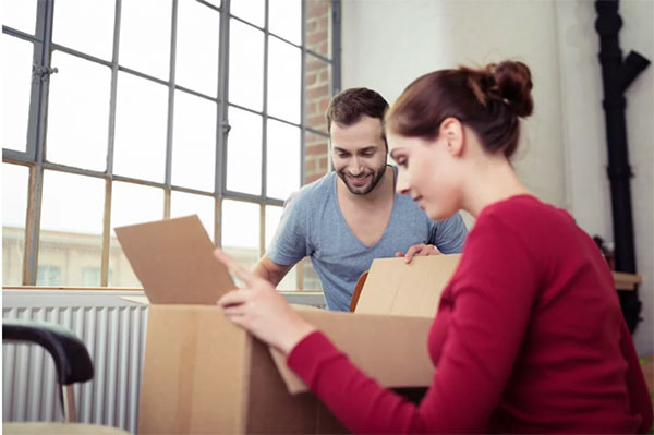 Couple packing boxes and planning to organize their reach in closet space