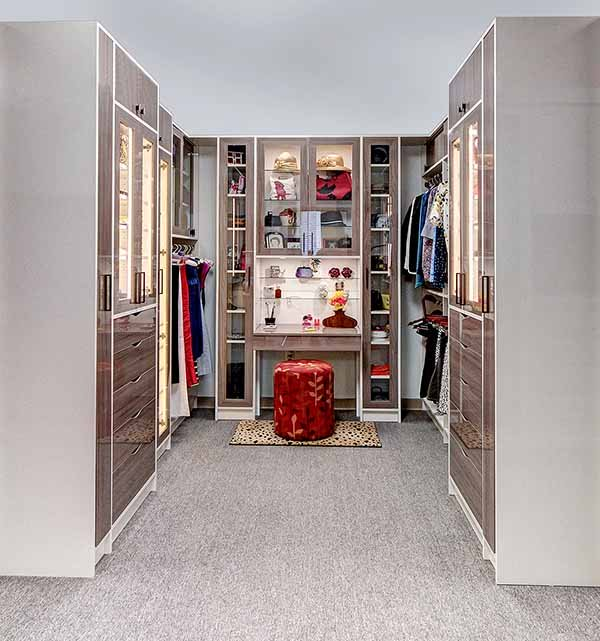 Walk-in closet space optimized with seating area and vanity