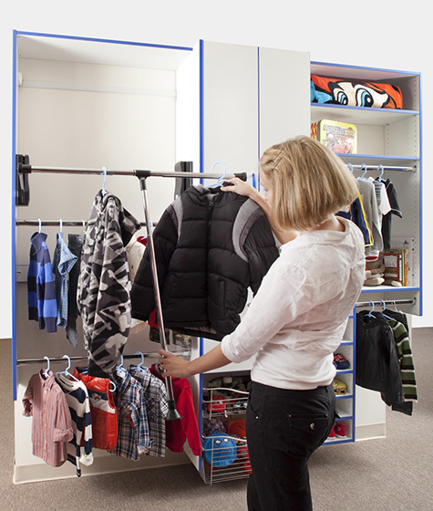 Woman using pull down closet rod to organize clothing