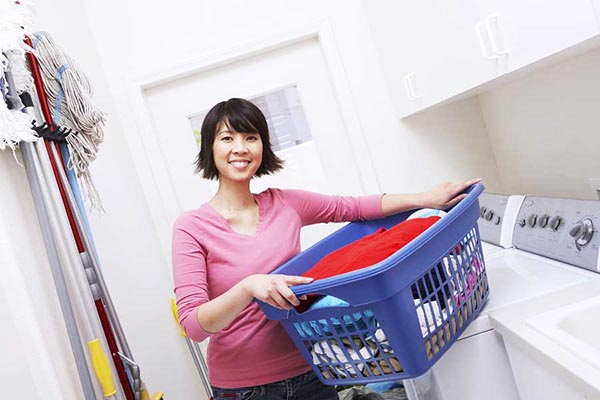 Asian woman carrying laundry basket filled with clothes