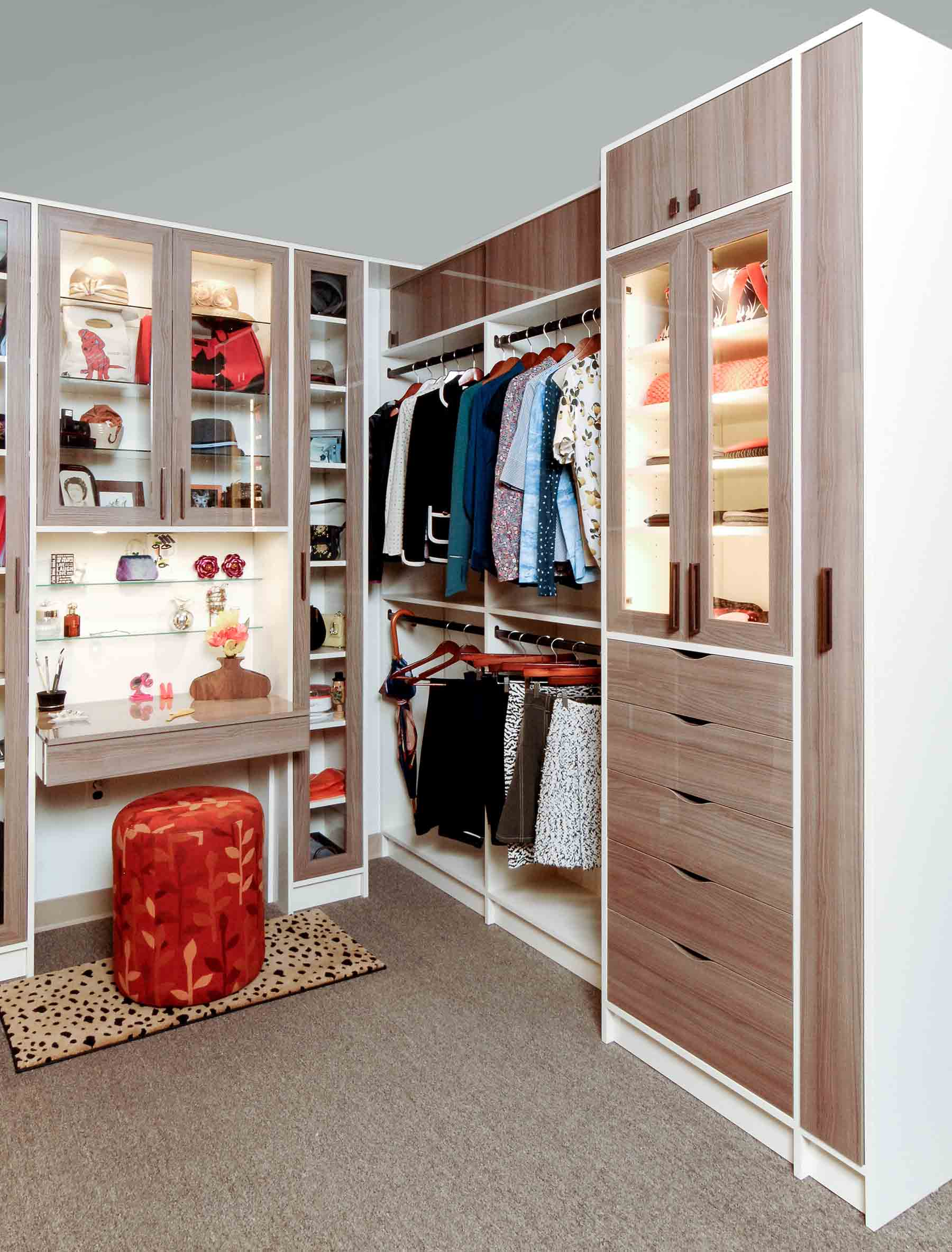 Custom closet design with vanity and sitting area