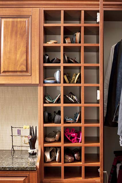 Closet with shoe cubbies filled with sandals and flip flops