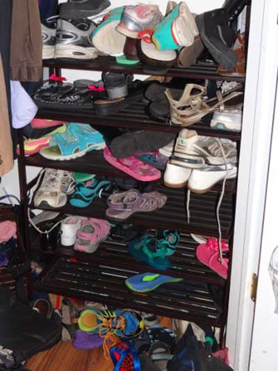 Before shoe closet picture with footwear disorganized