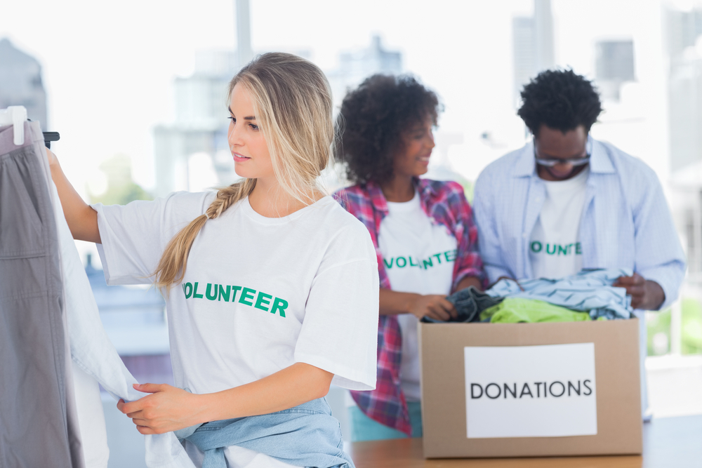 Woman donating clothing and placing in boxes