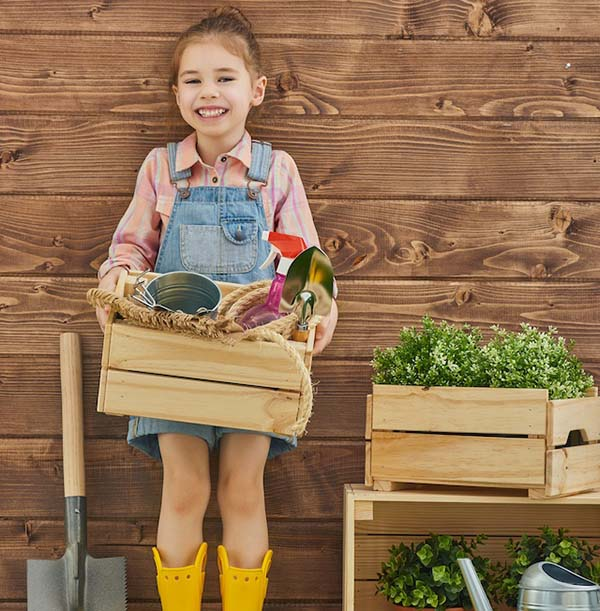 Cute child caring for her garden