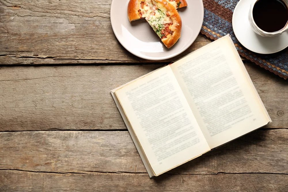 Book open on table with coffee and pizza