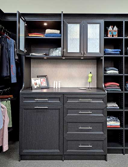 Walk-in closet with custom cabinet and countertop and puck lighting above