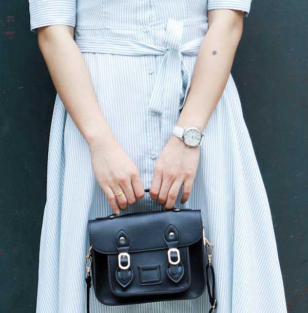 Woman holding fashionable black handbag with buckles looking like new