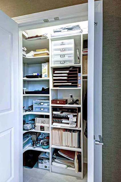 Reach in closet with office supplies stored on shelves