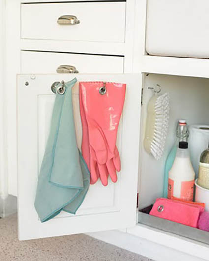 Cleaning supplies hung on hooks and on slide out shelf underneath sink