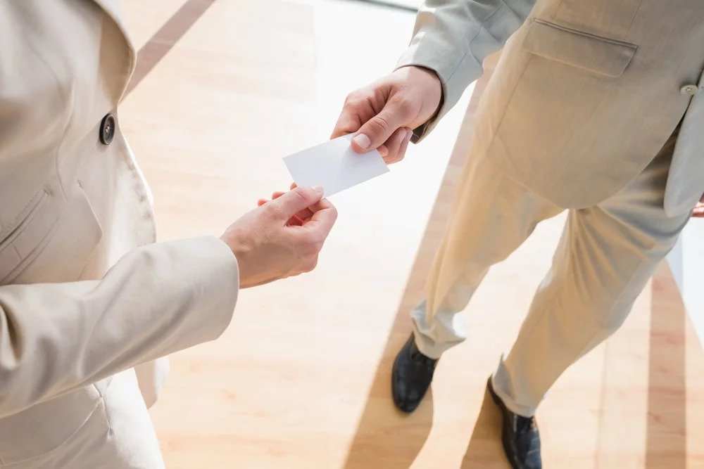 Businessman passing his card to businesswoman to be digitized