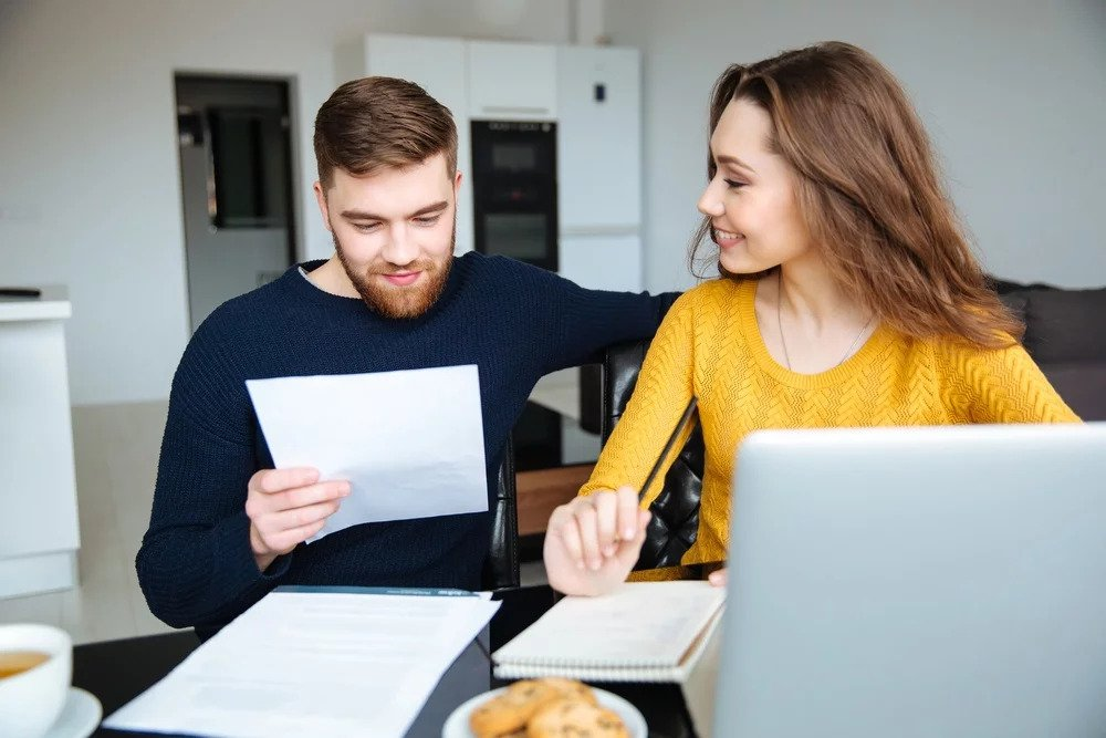 Happy young couple digitizing bills at home to declutter