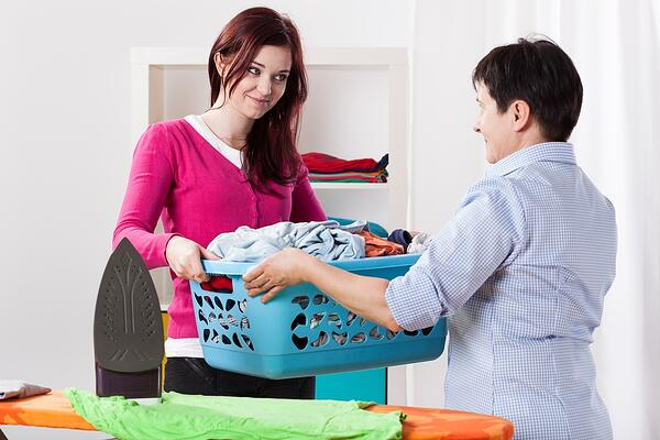 Mom handing duaghter the laundry to wash