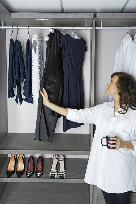 Beautiful young woman choosing an outfit from newly installed closet