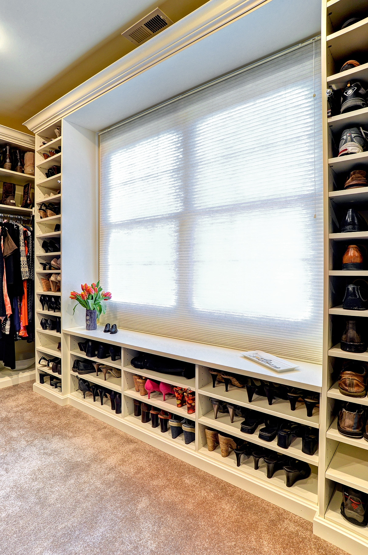 Reach in closet with shoes organized around window