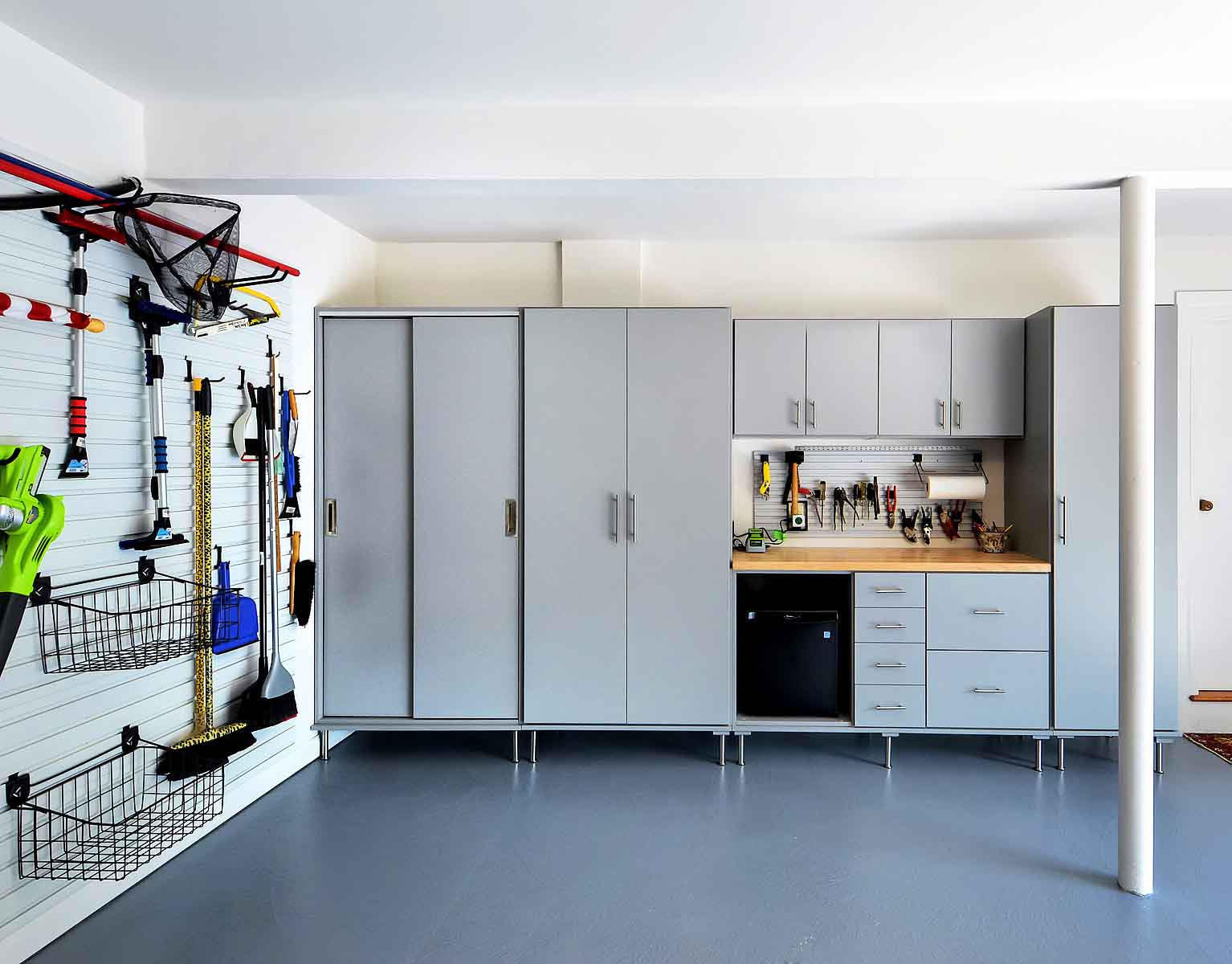 Organized garage with cabinets and wall system