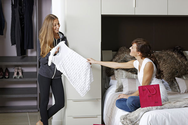 Two friends going through clothes and decluttering