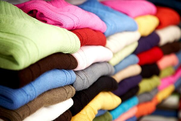 Colourful sweaters stacked neatly and folded on shelves