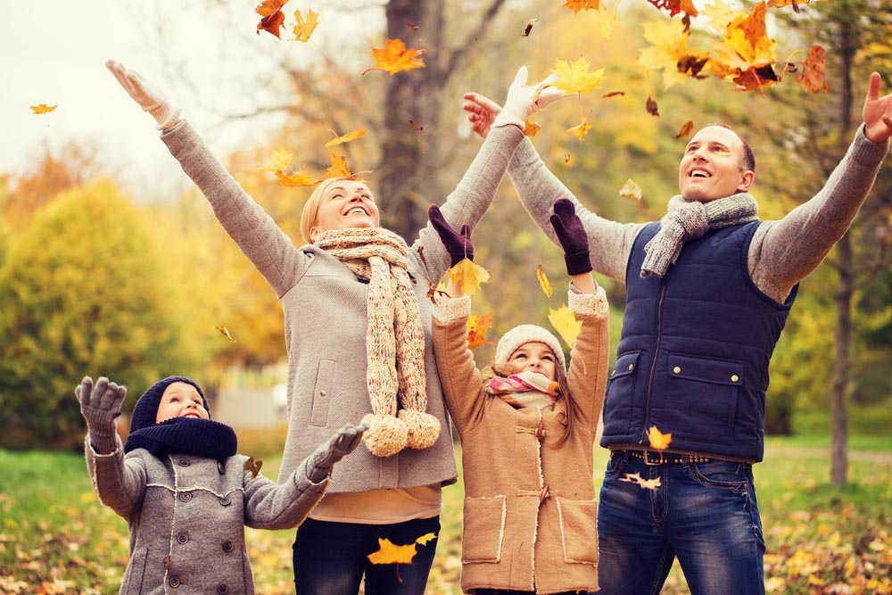 Family throwing leaves in the arie wearing fall attire