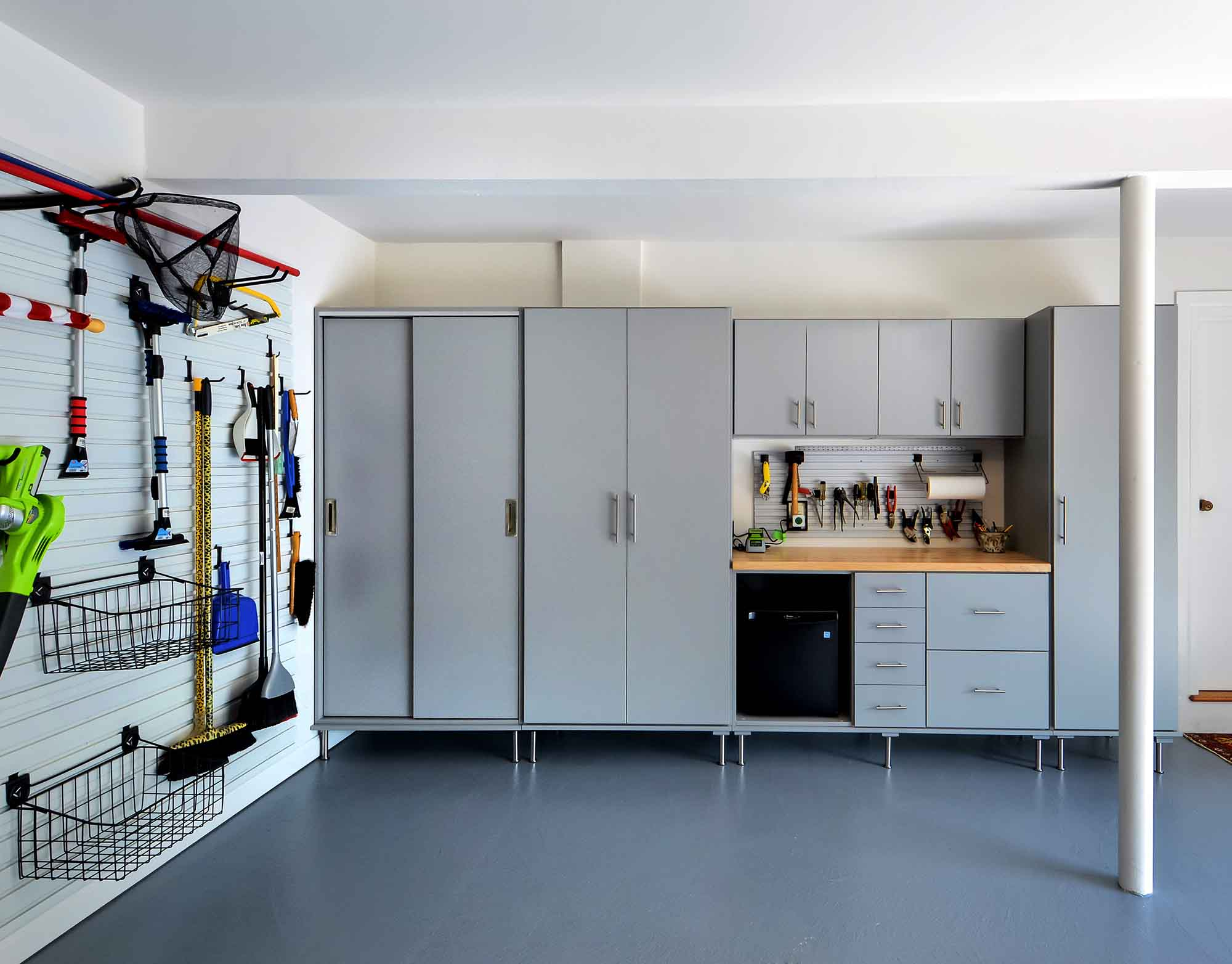 Organized garage with storwall system and cabinets