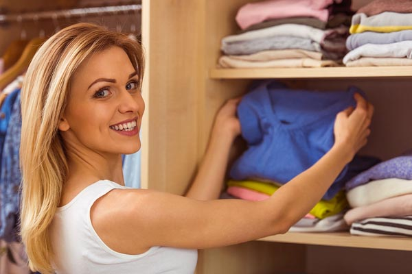 Woman organizing clothing in reach-in closet