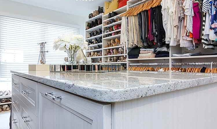 Granite countertop on top of a center island in walk in closet