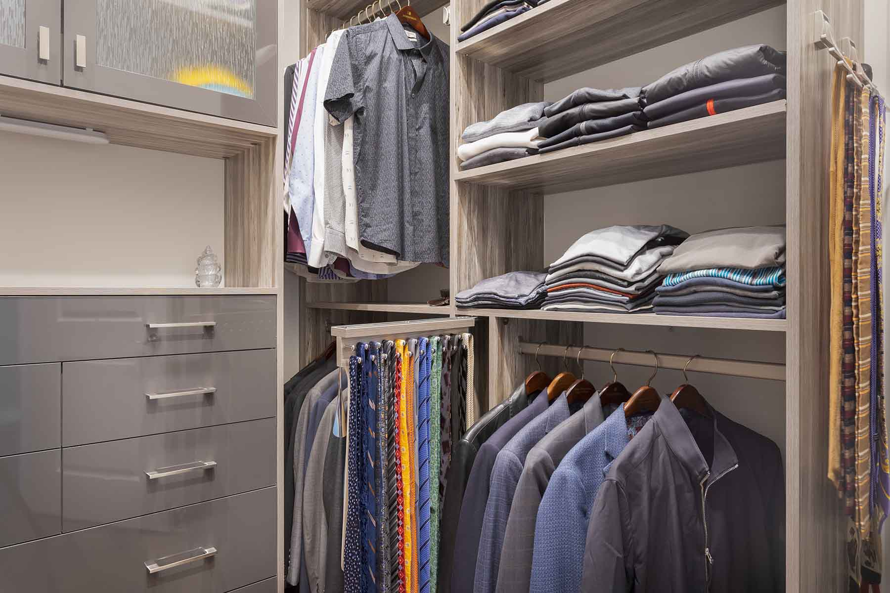 His walk-in closet with clothing organized