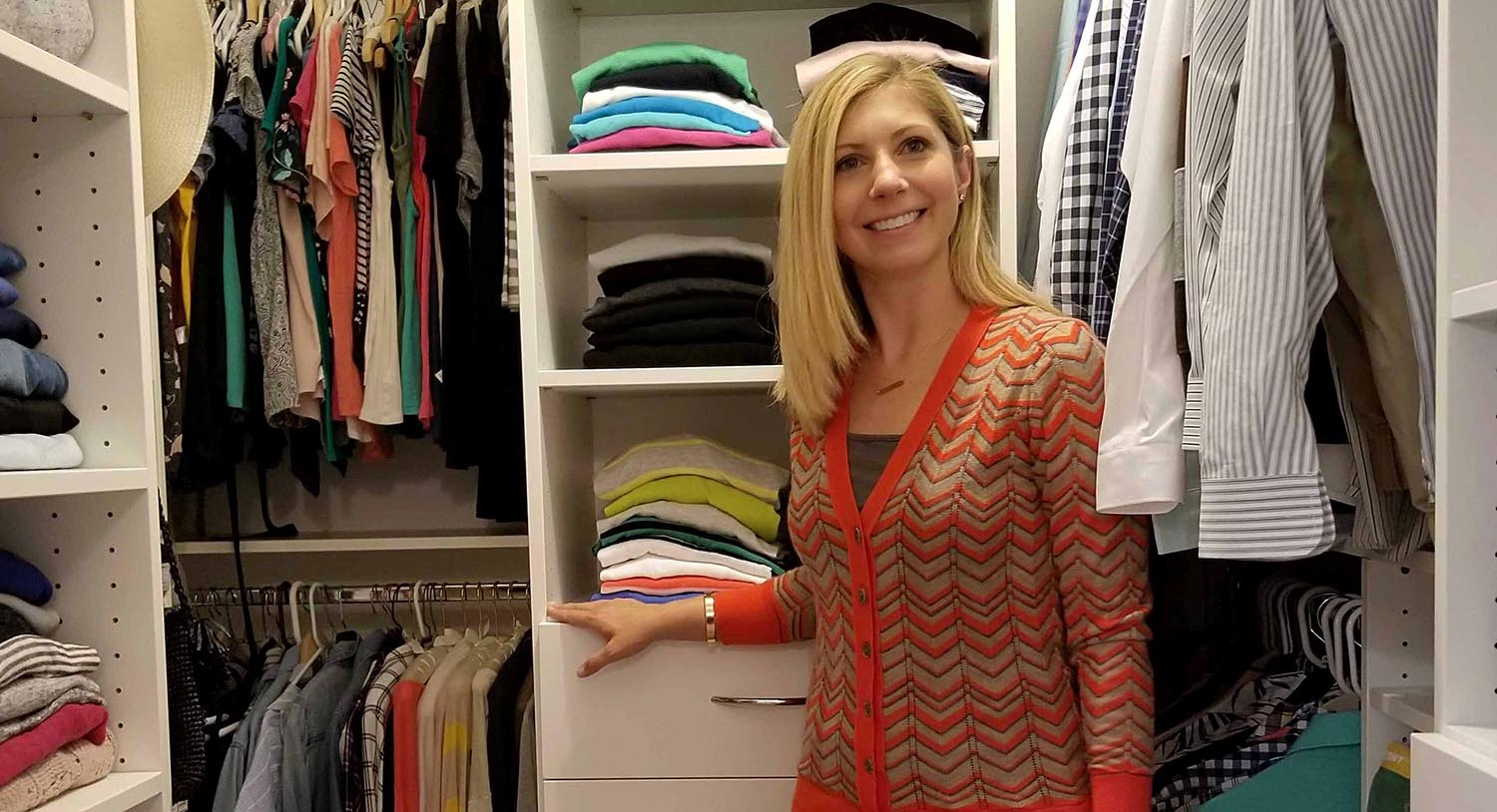 Woman happily standing in front of her organized closet