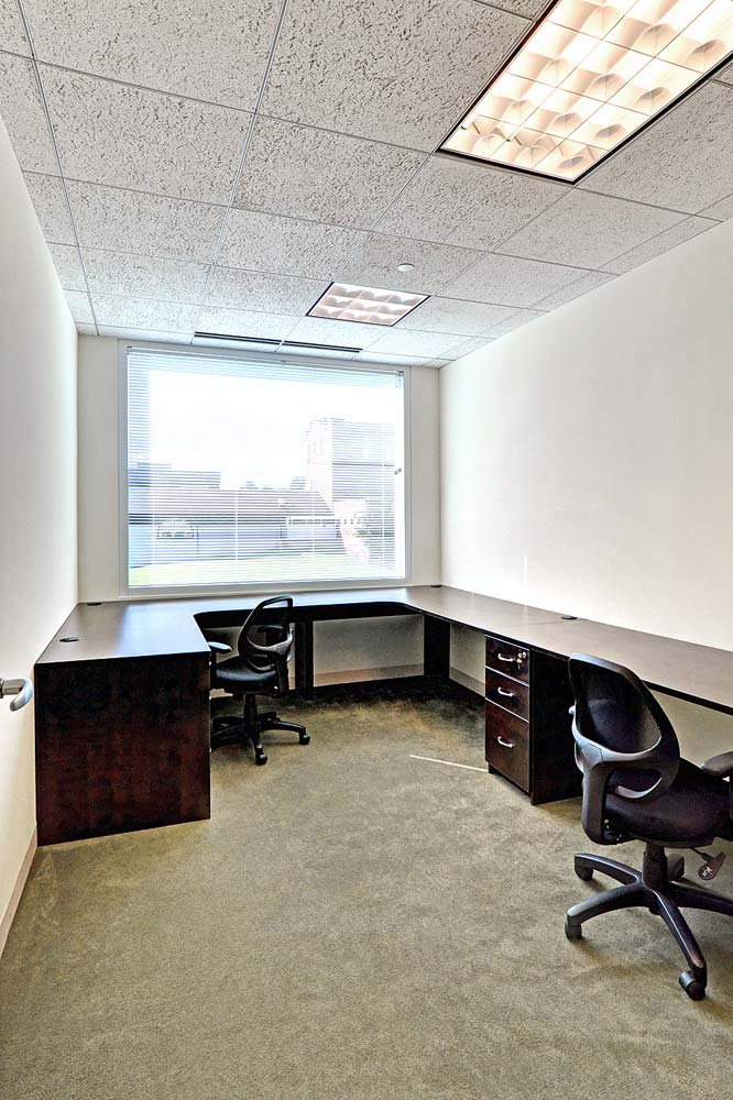 Custom commercial office with several wraparound workspaces and window