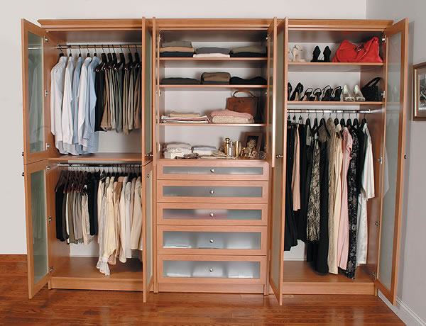 Custom built wardrobe closet with doors open and clothes neatly hung