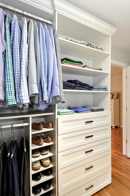 Walk-in closet organization system with shoe cubbies and clothes folded neatly on shelves