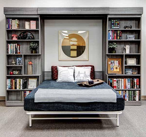 Murphy bed folded down from open bookshelf