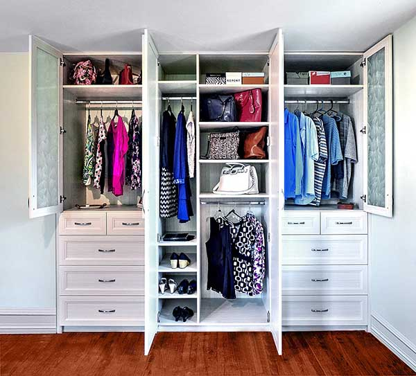 Custom built wardrobe closet with clothing items neatly hung and oragnized