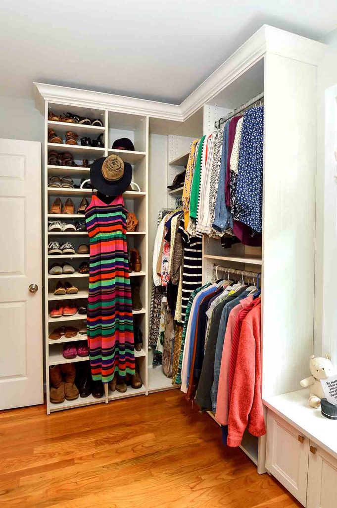 Walk in closet with tall vertical shoe shelves and clothes organized