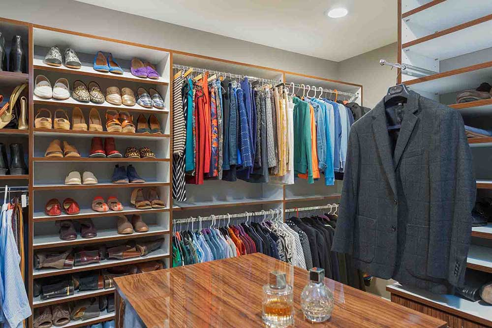 Walk-in closet with center island and organized shoe shleves