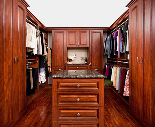 Walk in closet organization system with beautful wood cabinets and bench