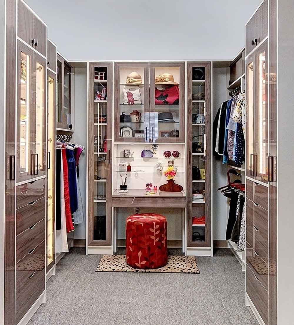 Beuatiful chic walk in closet finished in a high gloss wood laminate