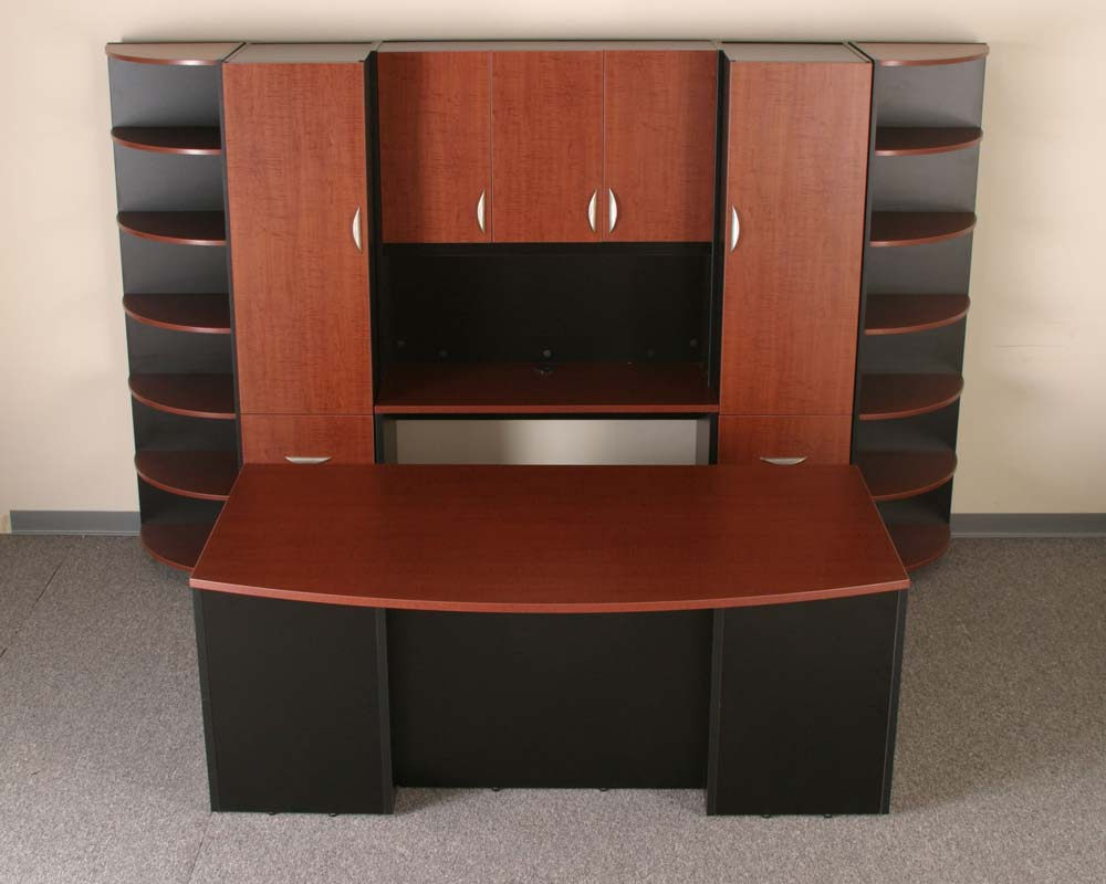 Custom home office design with cabinets and rounded shelves
