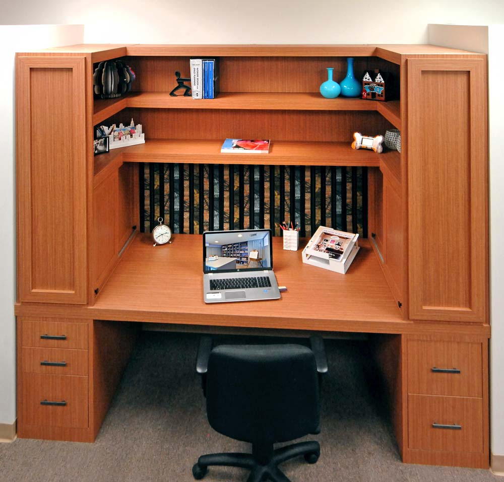 Desk cubicle in office with custom shelving and tack board