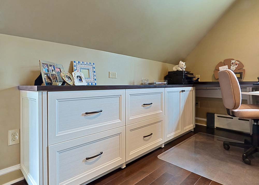 Custom built cabinet with deep drawers along angled wall in home office space
