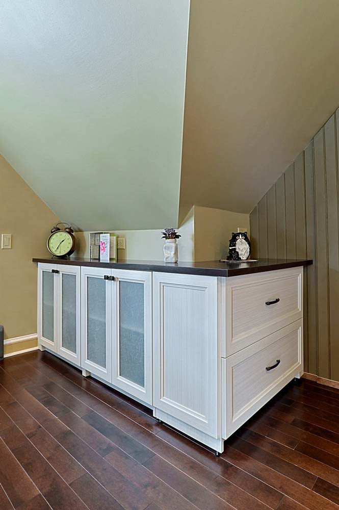 Home office with custom built wraparound cabinet around an angled corner space
