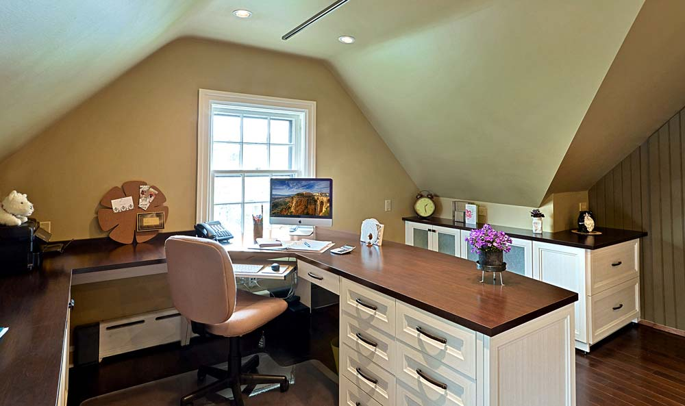 Home office with angled ceilings and custom furniture