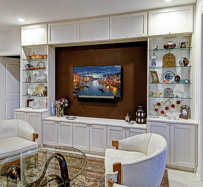 Custom media center and wall unit with glass shelves and custom cabinets