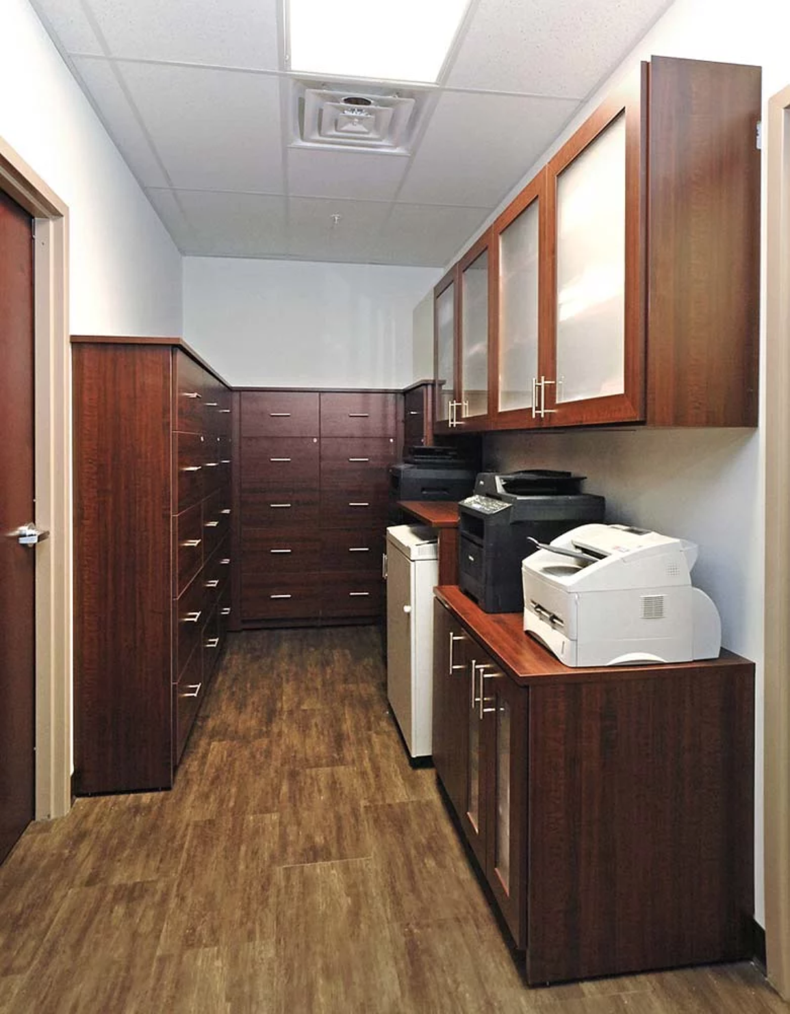 Custom built furniture cabinets housing office equipment and supplies