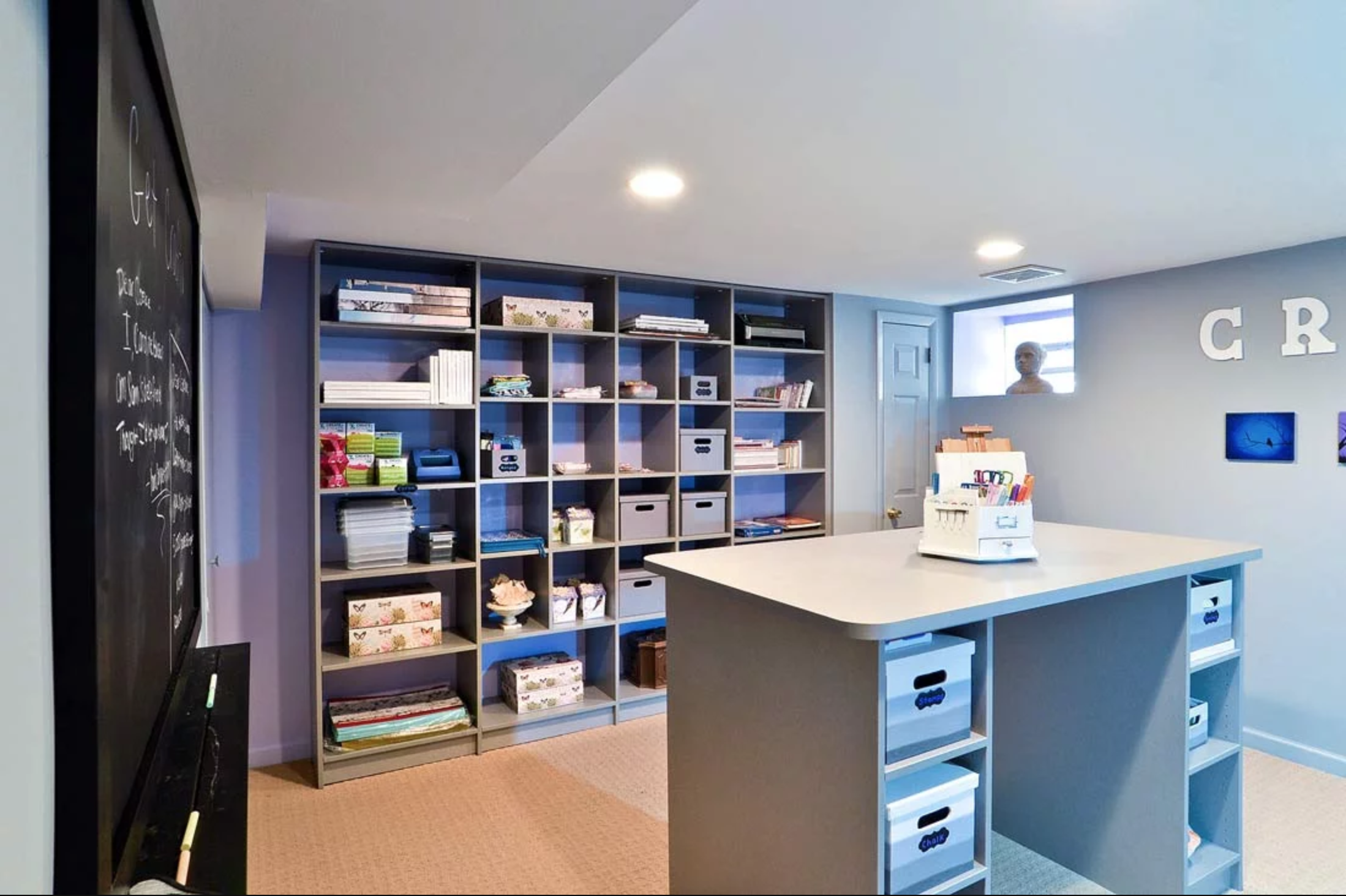 Custom craft room with open storage and large center desk work area