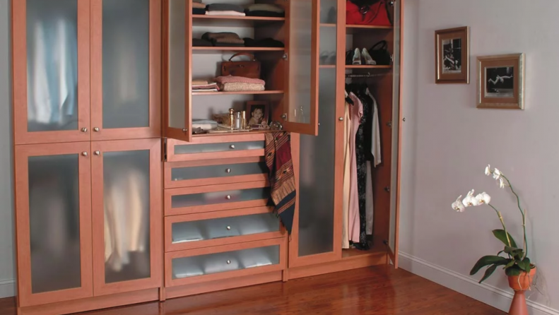 Classic style wardrobe with glass doors open to reveal organized clothing items