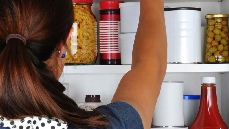 Woman reaching for items on neatly organized pantry shelf